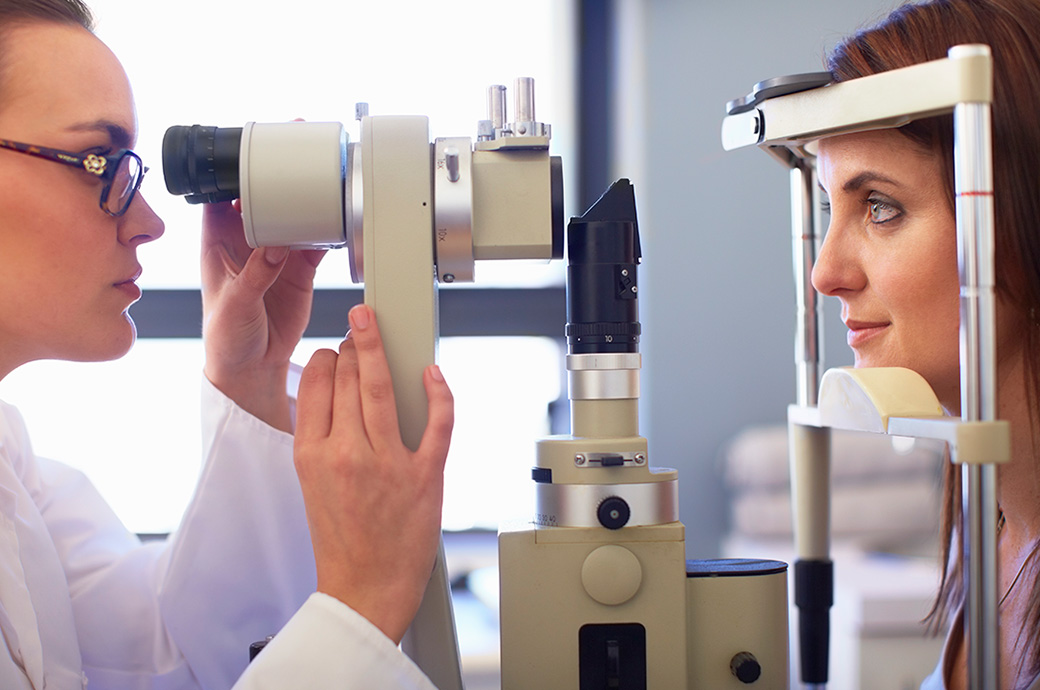 A side view of an eye doctor and a young woman looking through a retinal camera