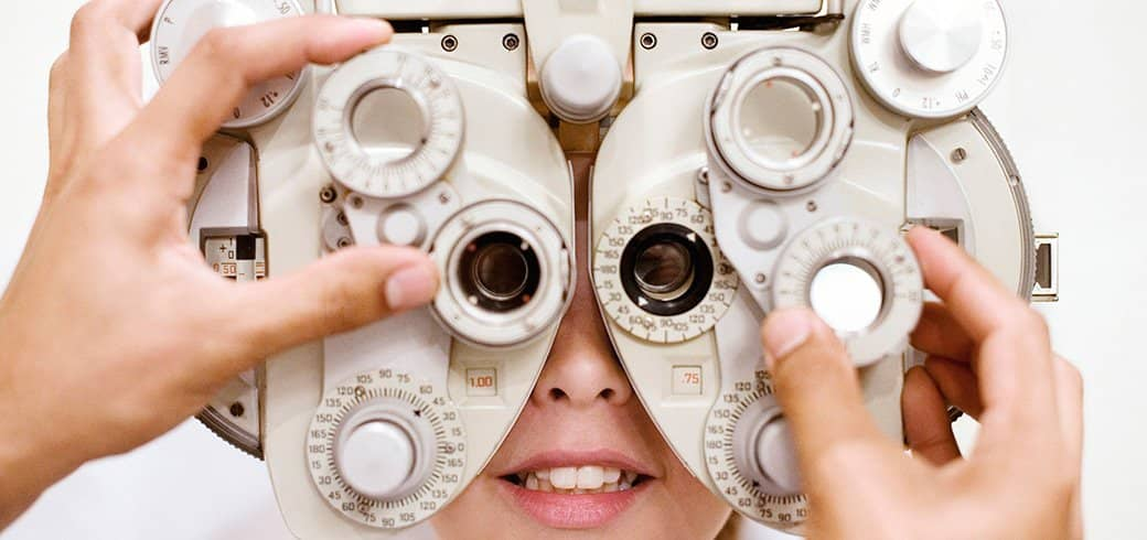 An eye doctor adjusts the phoropter as a young woman looks through
